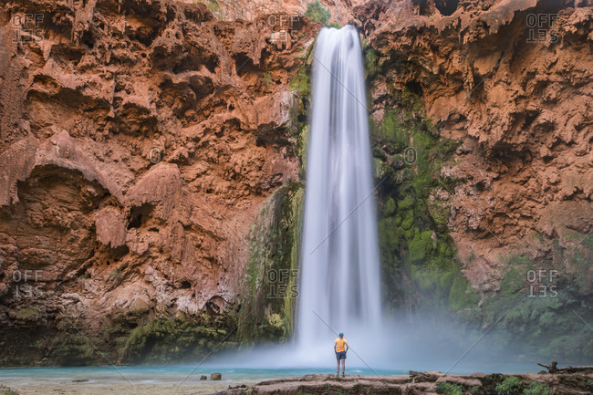 Beautiful natural scenery with lone man standing below Mooney Falls, Supai, Arizona, USA