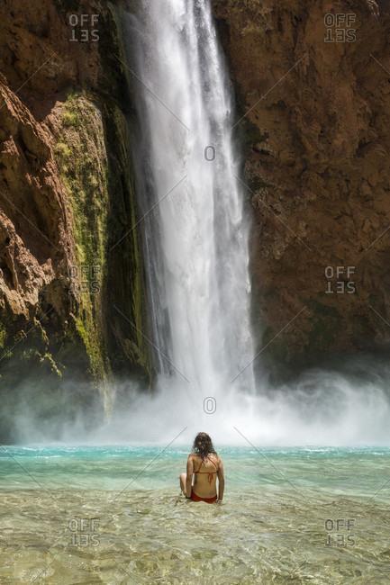 Rear view of woman in bikini swimming below Mooney Falls, Supai, Arizona, USA