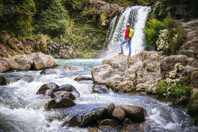 Lone female backpacker standing in front of Tawhai Falls, Tongariro National Park, Waikato, New Zealand