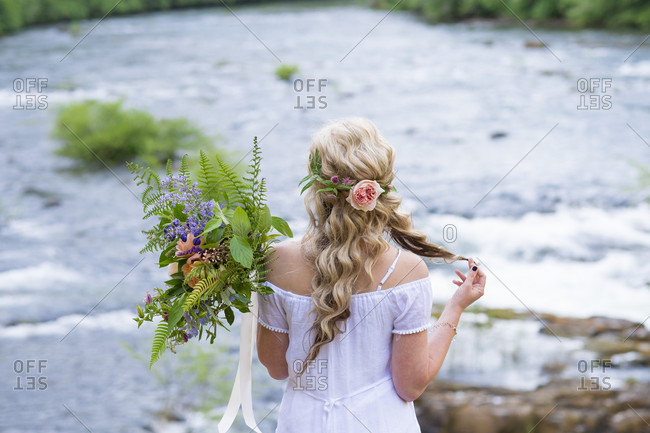 Bride standing on the edge of a cliff overlooking the North Umpqua River near Glide Oregon