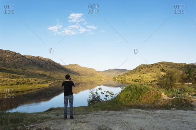 Teenager photographing River Douro and surrounding landscape with smart phone, Portugal