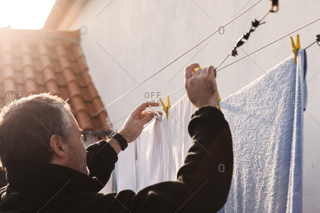 Man hanging laundry on clothesline outside house