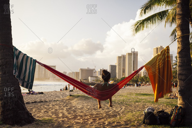 A hispanic adult relaxes in a hammock on Waikiki Beach, Hawaii as the sun begins to set on a warm, summer evening