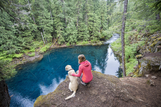 Woman with dog in natural scenery above Blue Pool, Oregon, USA