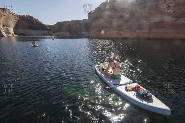 Rear view of woman looking at map while sitting on stand-up paddleboard, Lake Powell, Utah, USA