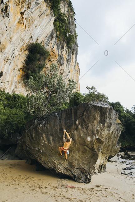A man boulders above a sandy beach, Thailand