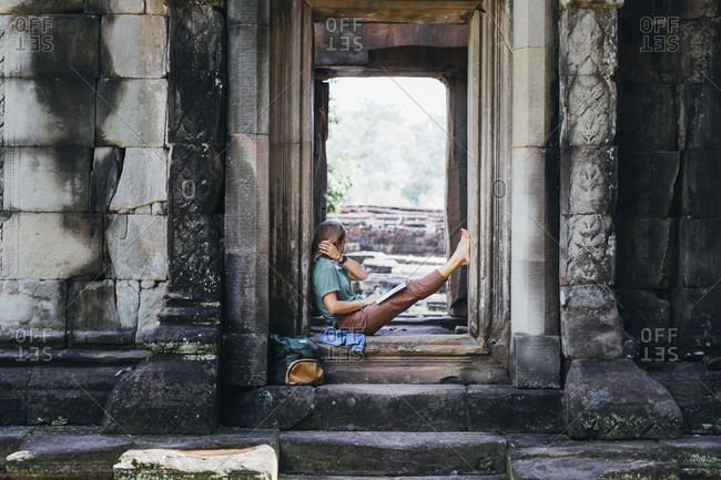 Girl is sitting in ancient ruins