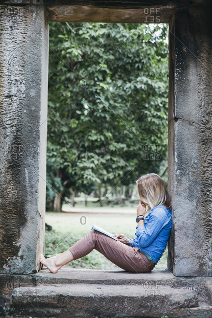 Girl is reading in ancient ruins