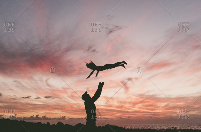 Silhouette of man throwing son into air at sunset, Valle Gran Rey, La Gomera, Spain