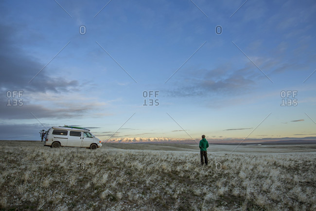 Sky over adult man standing alone in vast empty grassland in front of parked van at dawn, Oregon, USA