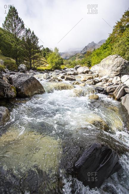 Stream flowing between rocks in upper parts of Pyrenees, Benasque, Huesca, Spain