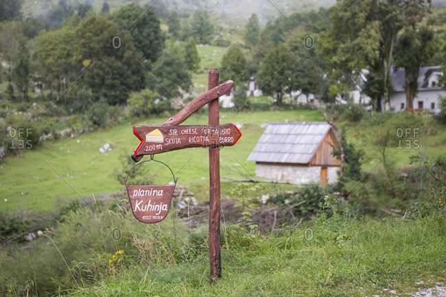 Rural scene with sign pointing way to mountain farm producing cheese in Triglav, Slovenia