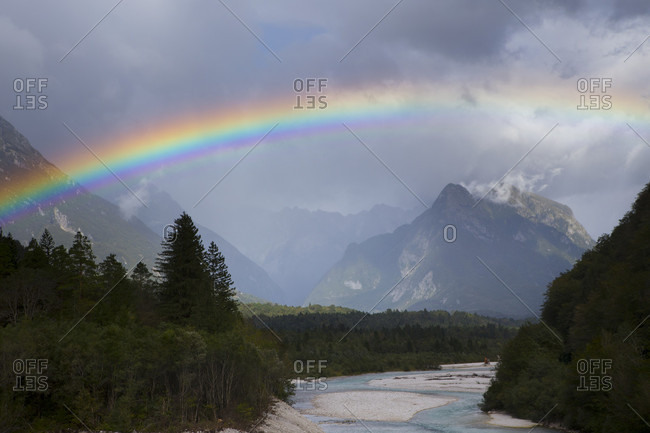 Majestic view of rainbow over Soca River with mountains in background near Bovec, Slovene Littoral, Slovenia