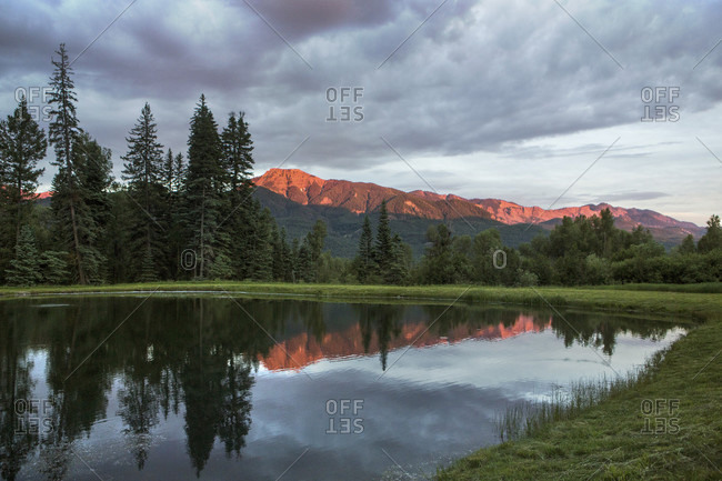 Scenic view of shiny pond in Blanco Basin reflecting clouds and surrounding trees at dusk, Colorado, USA