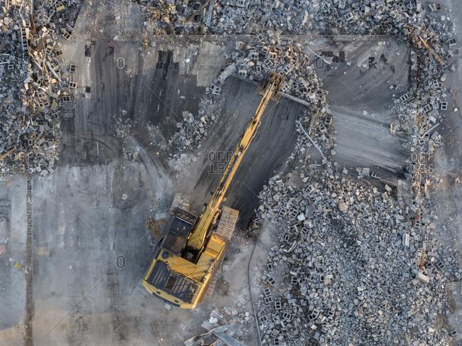 Excavator cleaning up debris from demolished supermarket, Lithonia, Georgia, USA