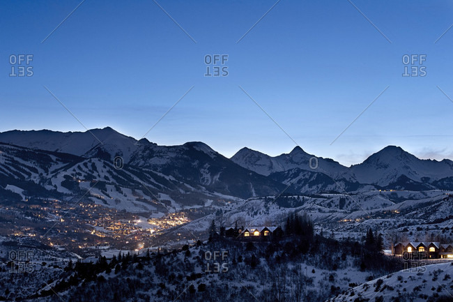 Clear sky over snowcapped hills and illuminated houses of Snowmass Village, Colorado, USA