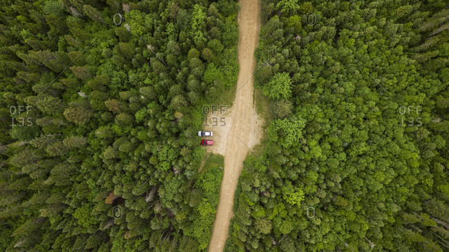 Aerial view of two cars in parking lot along dirt road surrounded by forest, Gaspe, Quebec, Canada