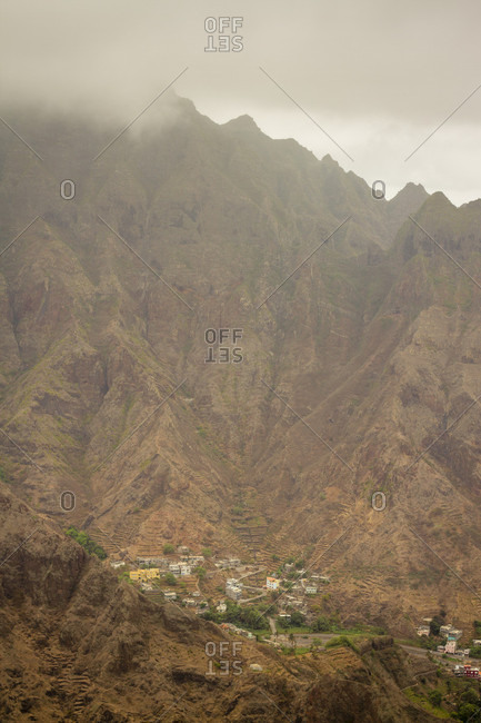 Clouds surround the top of a mountain in Cape Verde, Africa, as a small village is nestled quietly in a valley below