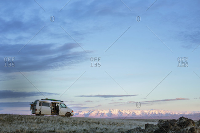 Sky over van parked in grassland at dawn with snowy mountain range in background, Oregon, USA