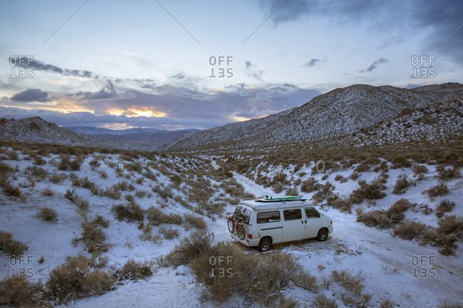 White van parked in front of snowcapped hills of High Desert, Bishop, California, USA