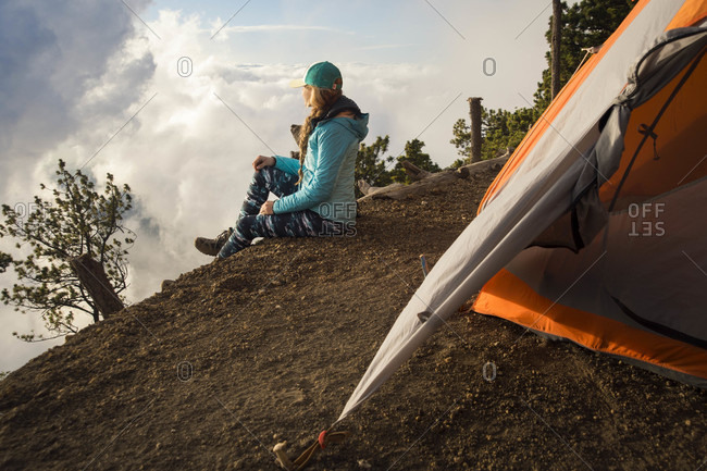 Side view of young female hiker sitting outside tent at summit of Acatenango Volcano, Guatemala