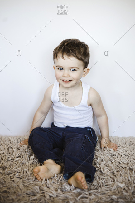 Toddler boy sits on thick carpet
