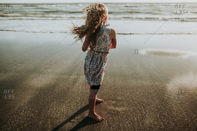 Back view of young girl standing barefoot in shallow beach tide