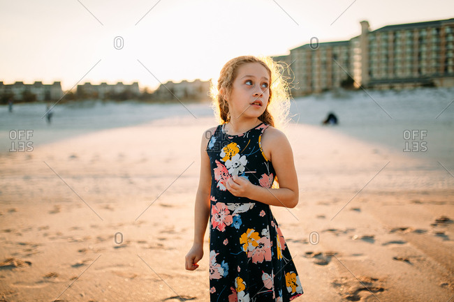 Blond curly haired girl standing on the beach in a floral sundress at sunset