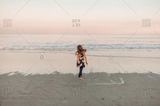 Long-haired girl in floral dress and leggings running towards shoreline