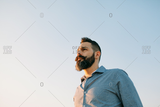 Lower angle view of young bearded man staring towards the sunset against a clear sky