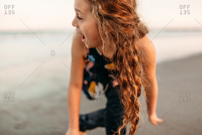 Adolescent girl with long curly hair having fun at the beach