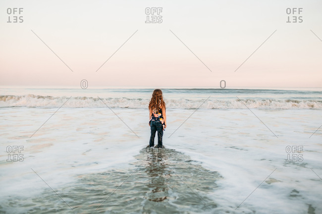 Curly haired girl standing in low tide watching waves from behind