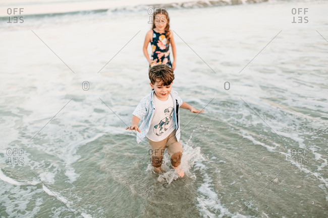 Brother and sister running through water on beach vacation