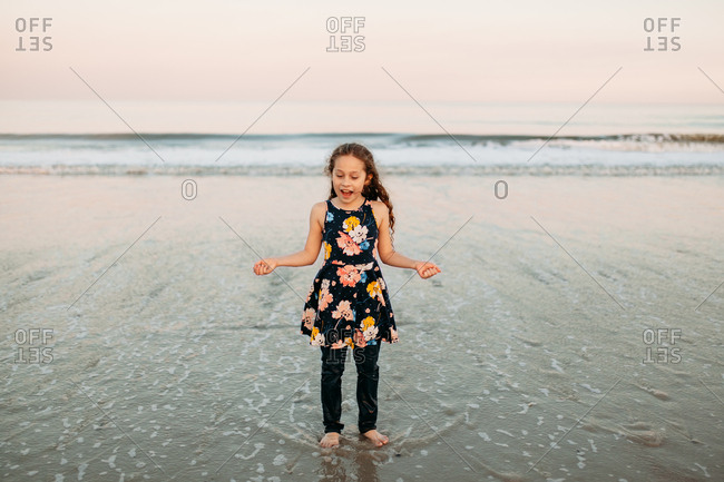 Enthusiastic girl with long curly hair playing at the beach