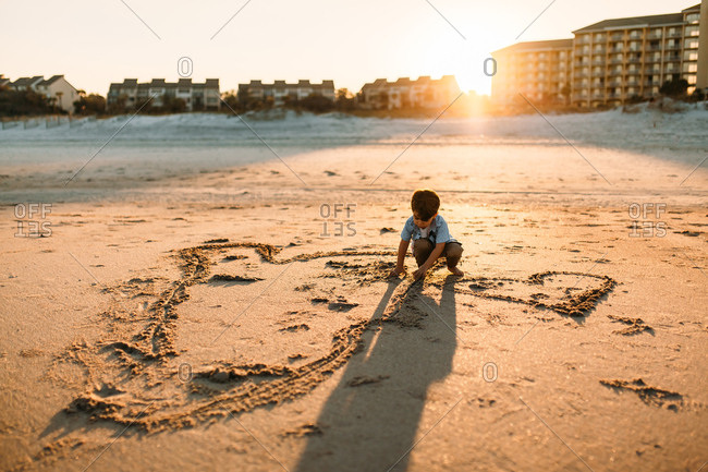 Cute toddler drawing hearts in sand at sunset