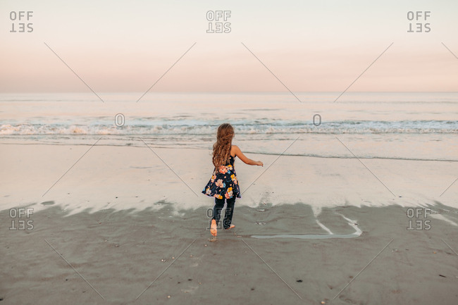 Back view of barefoot girl running to the beach shore at dusk