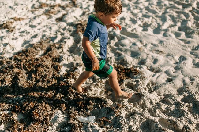 Small soaking-wet toddler running through sand