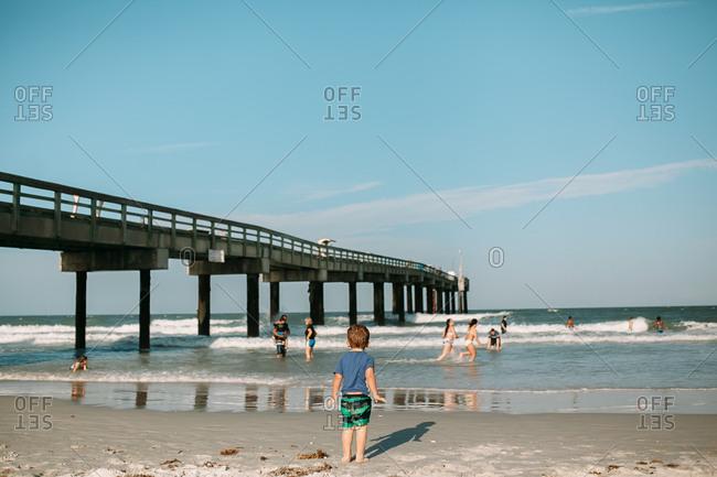 Careful toddler watching older kids playing in the ocean