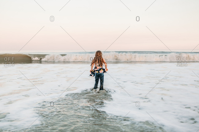 Preteen girl waiting for waves splashing in alone at the beach