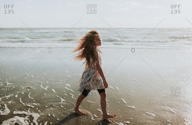 Adolescent girl walking with determination towards sunlight on breezy beech