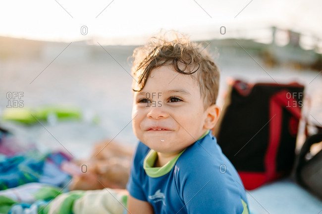 Happy toddler smiling off camera on beach picnic blanket