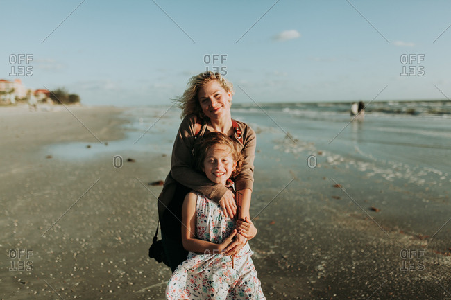 Proud mother posing for vacation portrait with daughter on the beach