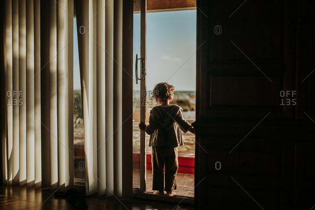 Little boy standing in glass door frame at sunset