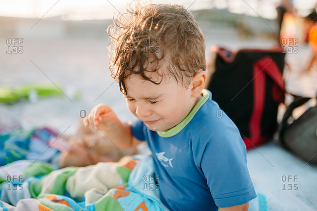 Toddler making uncomfortable face on beach blanket