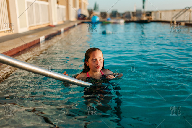 Girl swimming alone in hotel pool at sunset