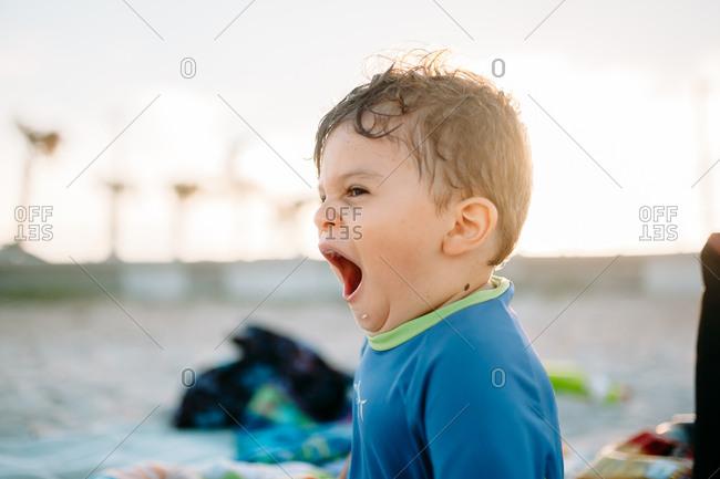 Tired toddler yawns after beach swim