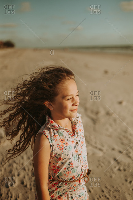 Adolescent girl watching sunset on windy beach
