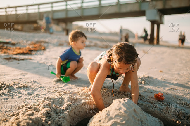 Siblings working on sandcastle together on beach vacation