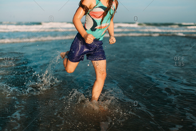 Cropped lower view of young girl running in shallow water at the beach