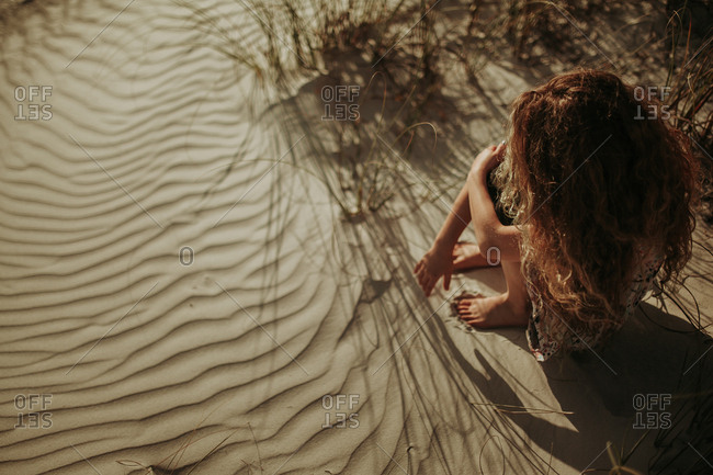Overhead view of adolescent girl sitting alone in the sand